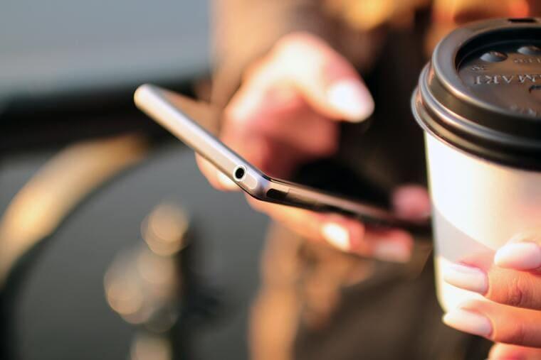 スマートフォンとコーヒーを持っている