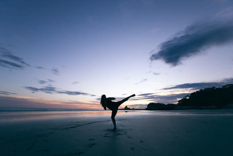 浜辺でキックする女性