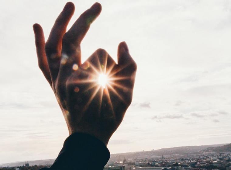 指から太陽を覗いている