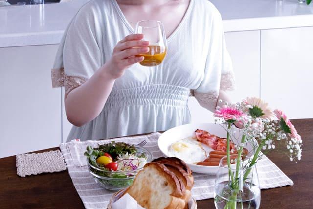 朝ごはんに豊潤サジーを飲んでいる女性